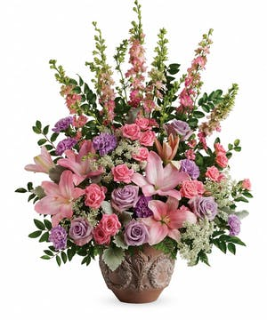 Sympathy arrangement of lavender roses, pink spray roses, pink lilies and more in a classical pot.
