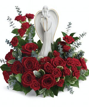 Angel keepsake surrounded by red roses and greenery.
