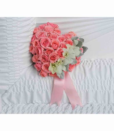 Casket insert of white orchids and pink spray roses accented with pink ribbon.