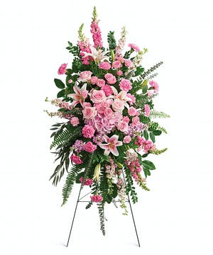 Sympathy spray of pink flowers accented with greenery and displayed on an easel.