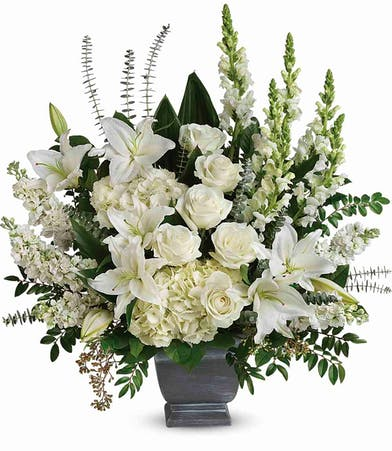 Sympathy bouquet of white roses, hydrangea, snapdragons, stock and more in a modern pot.