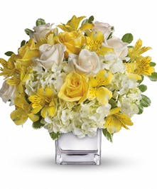 Yellow and white flowers in a clear glass cube vase.
