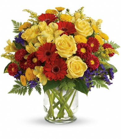 Yellow, purple and red bouquet of flowers in a clear glass vase.