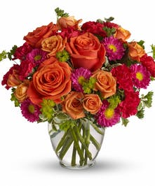 Orange roses and spray roses, asters, hot pink mini carnations and more in a clear glass vase.
