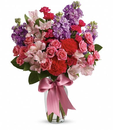 Pink roses and spray roses, light pink alstroemeria, hot pink miniature carnations, lavender stock and salal in a clear glass vase with ribbon tied around.