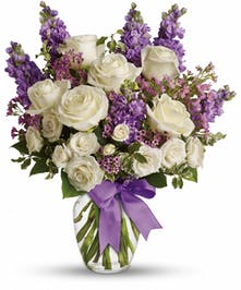 White roes and lavender in a clear glass vase tied with a purple ribbon.