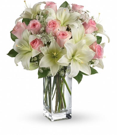 White lilies and pink roses in a tall glass cube vase.