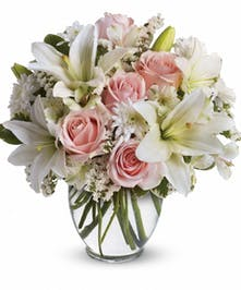 Pastel pink roses, white lilies and more in a clear glass vase.