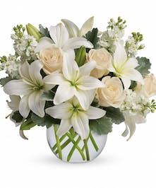 Crème roses, white asiatic lilies and stock stem in a glass bubble vase.