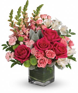 Clear cube vase of hot pink roses, white alstroemeria, pink mini carnations and more.