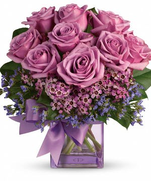 Lavender roses and waxflower, purple limonium and greens in a purple cube vase.