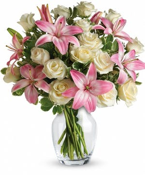 Roses and lilies with greenery in a clear glass vase.