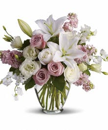Pink and white roses, white lilies, pink stock, and sweet peas in a clear glass vase.