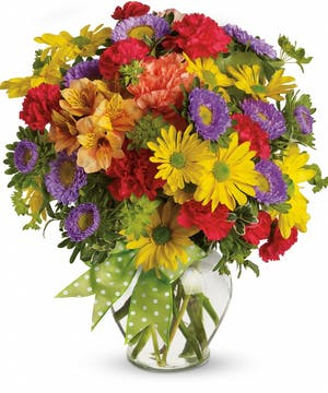 Yellow, red, purple and orange mixed flowers in a clear glass vase with a green polka dot ribbon.