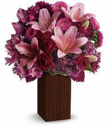 Bamboo vase filled with pink lilies, purple alstroemeria and chrysanthemums, red roses and more.