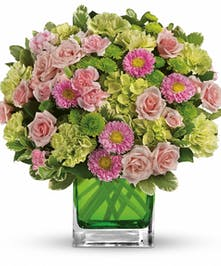 Green and pink flowers arranged in a green cube vase.
