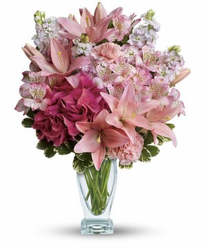 Pink lilies and hydrangea in a clear glass vase.