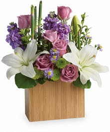 Bamboo cube vase of lavender roses, white asiatic lilies, lavender stock and more.