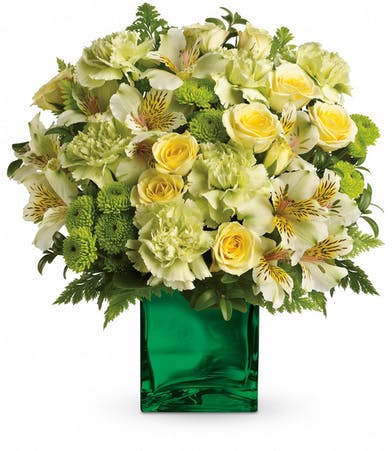 Emerald mirrored cube vase filled with yellow roses, alstroemeria, green carnations and button spray chrysanthemums.