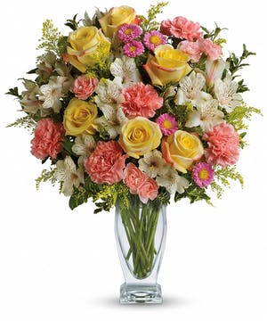 Yellow roses, pink carnations, white alstroemeria and pink asters in a clear glass vase.