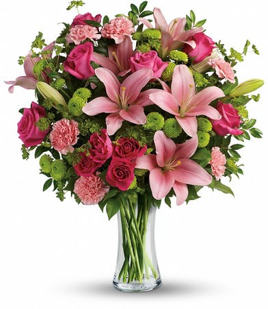 Hot pink roses, hot pink spray roses, pink asiatic lilies, pink carnations, green button spray chrysanthemums, bupleurum, huckleberry and lemon leaf in a clear glass vase.