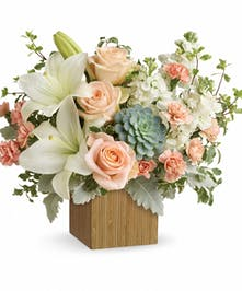 Lilies, roses, carnations and succulents in a sleek bamboo box.