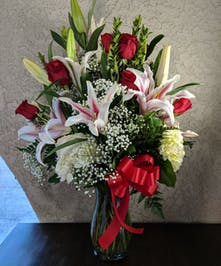 Hydrangea, lilies and long stemmed red roses in a clear glass vase tied with a red bow.