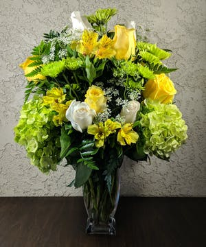 White roses, yellow spray roses, green carnations, green button spray chrysanthemums and white waxflower in a clear glass vase.