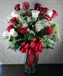 Red and white roses with Queen Anne's Lace in a clear glass vase with a red ribbon.