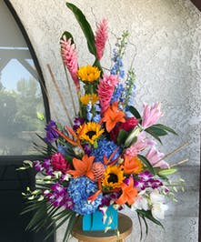 Tropical flower arrangement made with orange lilies, pink lilies, ginger, white and purple orchids, purple lisianthus, delphinium, birds of paradise and  hydrangeas.