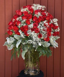 100 Long stemmed red roses in a clear glass vase.