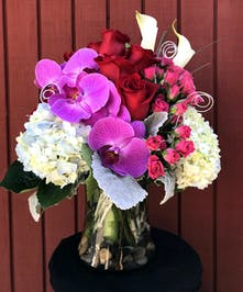 Modern flower arrangement of red roses, pink spray roses, white hydrangea, mini calla lilies, and purple phalaenopsis orchid in a glass vase.