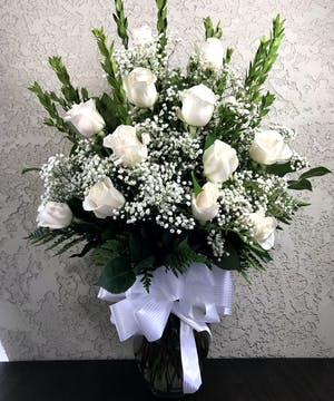 One dozen white roses in a clear glass vase.