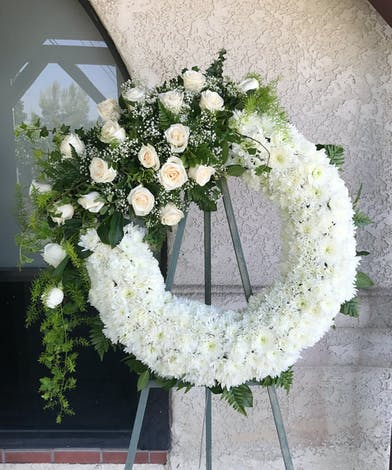 A ring of white poms accented with white roses, ribbon and subtle greenery.
