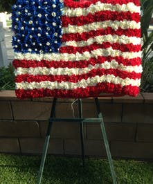 Patriotic funeral flower design with red, white and blue flowers in the shape of the American flag.