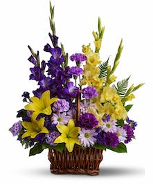 Sympathy basket of purple and yellow flowers.
