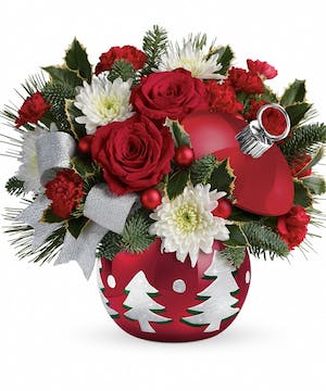 Ornament container of red and white flowers and winter greenery topped with a bow.