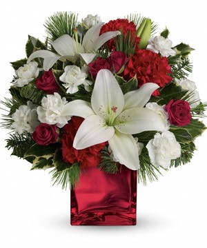 Red spray roses, white asiatic lilies and red carnations in a red mirrored cube vase.