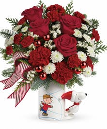 PEANUTS® Christmas mug filled with red and white flowers, greenery and small glass ornaments.