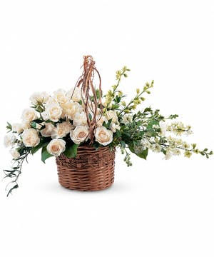 Wicker basket of white carnations, larkspur, roses and greenery.