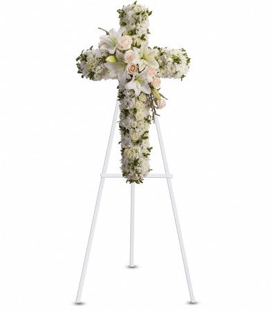 Sympathy cross of creme roses, lilies, stock and more presented on an easel.