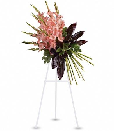 Sympathy spray of coral gladioli and greenery.