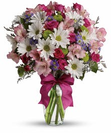 Pink, purple, white and green flowers in a clear glass vase tied with a hot pink bow.