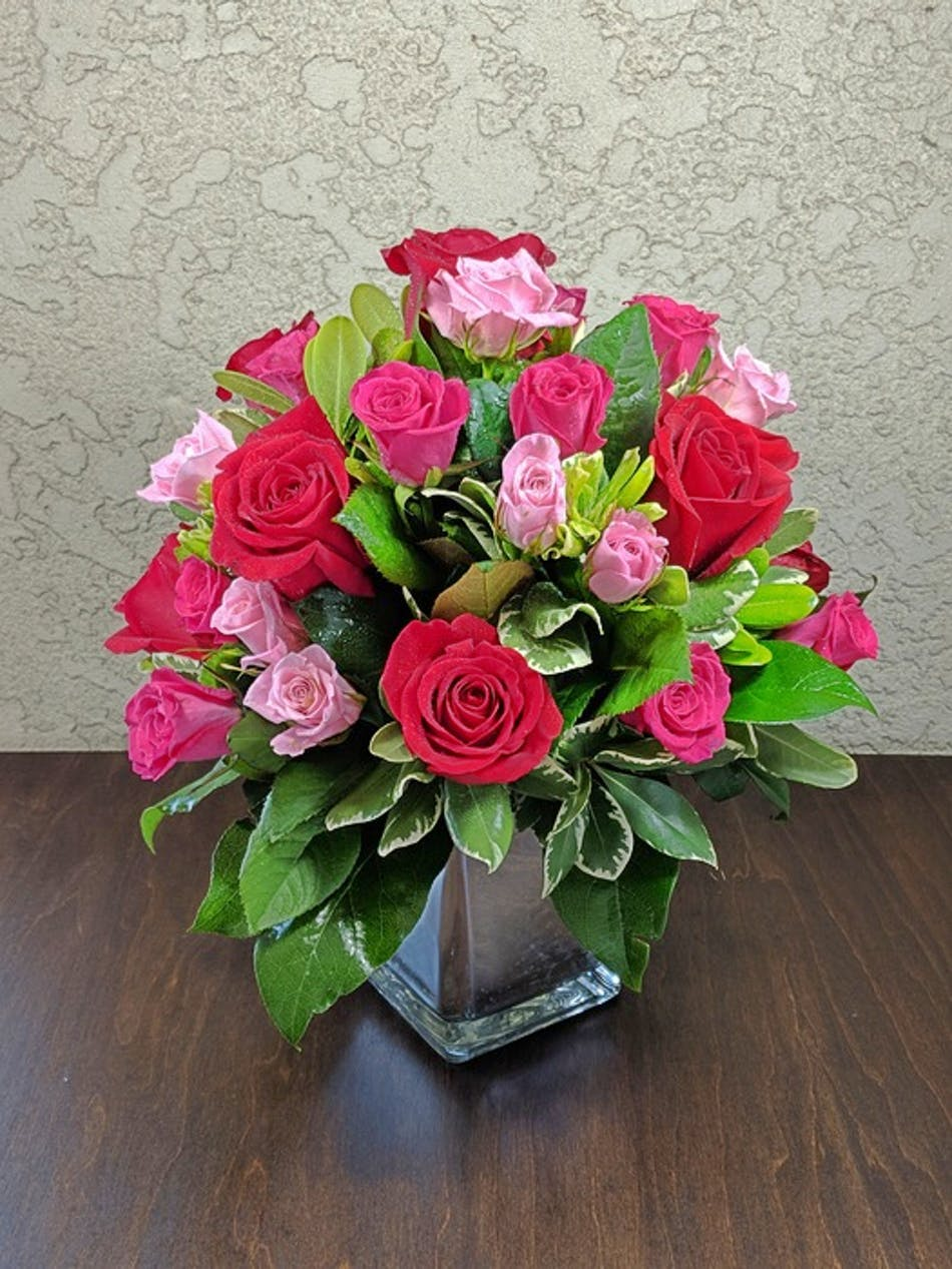 Red and pink roses with greenery in a glass cube vase.