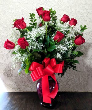 One dozen red roses and baby's breath in a clear glass vase.