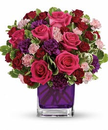 Violet glass cube filled with hot pink roses, purple carnations, and pink mini carnations with greenery.