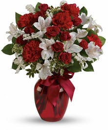 Red vase filled with red spray roses, white alstroemeria, and red carnations tied with a red satin ribbon.