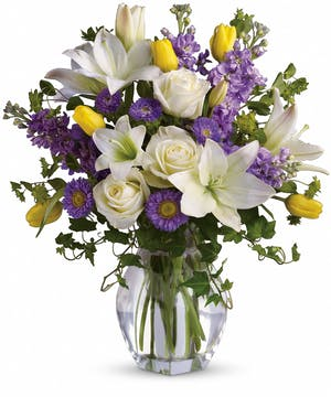 Yellow, white and purple flowers in a glass vase.