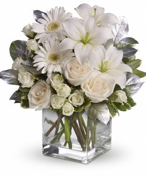 Clear glass cube vase filled with white flowers.