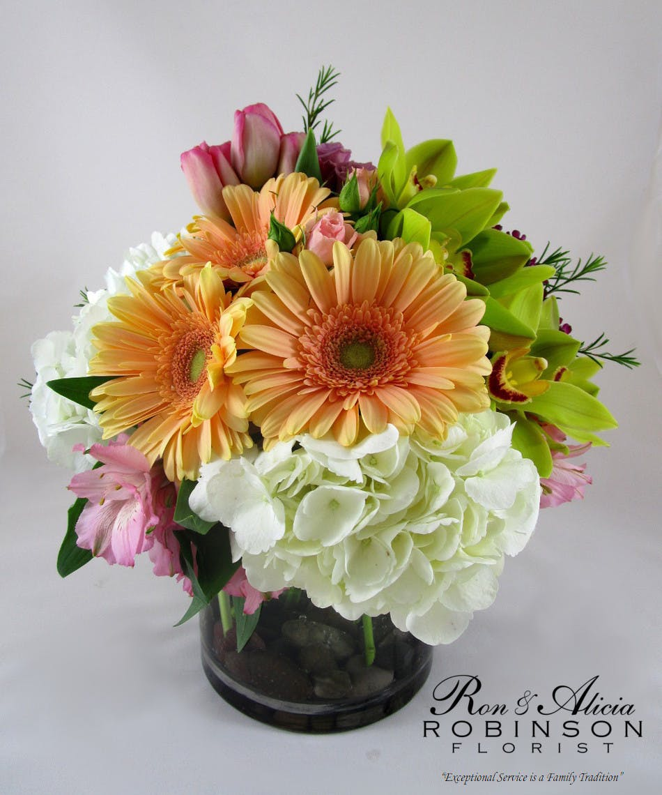 Orange, green, pink and white flowers in a glass cylinder vase